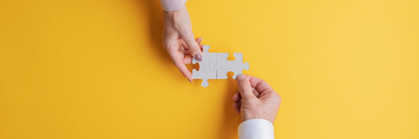 Wide view image of male and female hand joining two matching puzzle pieces together in a conceptual image of teamwork and cooperation. Top view with copy space.